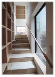 シンボルの階段1。1F土間から中間の踊り場。壁は構造体現しとなっています。